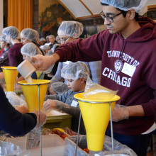 A student helps pack meals at a volunteer event.