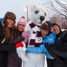 A group of four students hug a person wearing a polar bear costume outside in the winter.