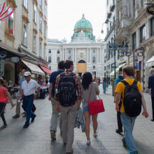 A group of students walk through a city square toward a palace in Vienna.