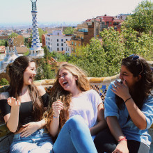 Three students laugh together on a bench in Parque Guell in Barcelona.