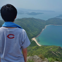 A male student views the coastline off Hong Kong from atop a mountain.
