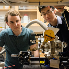 Two students post with their levitation experiment inside a physics lab.
