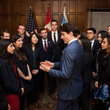 A group of students speak with Prime Minister Justin Trudeau as part of an event hosted by the Institute of Politics