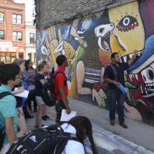 A group of students stand in front of a mural on a wall in a neighborhood in Chicago.