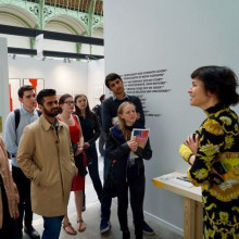 A group of students in Paris converse with a staff member in an art museum.