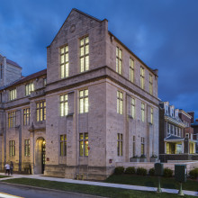 A street photo of the outside of the Neubauer Collegium building at dusk.
