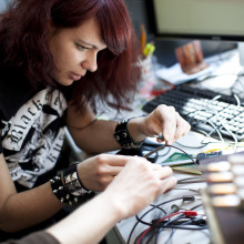 Two students work on a set of wires in a lab.