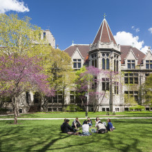 A group of students sit in a circle outside in front of a gothic-style building.