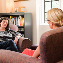 A female student seated in a red chair speaks with a female counselor.
