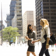 Two female students dressed in suits walk by a fountain in downtown Chicago.