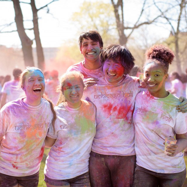 A group of students post outside covered in colorful powder during Holi, a Hindu spring festival.