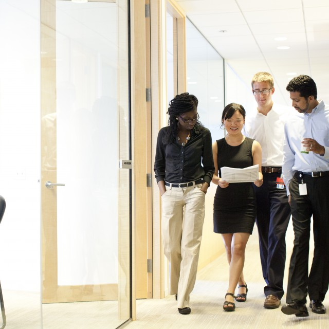 A group of four interns review a paper as they walk through the hallway of an office.