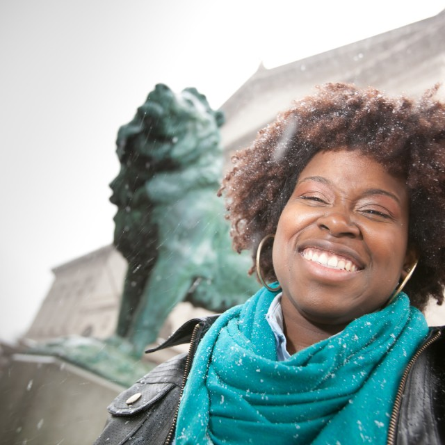 A close-up of a grinning female-appearing person in front of a bronze lion statue.