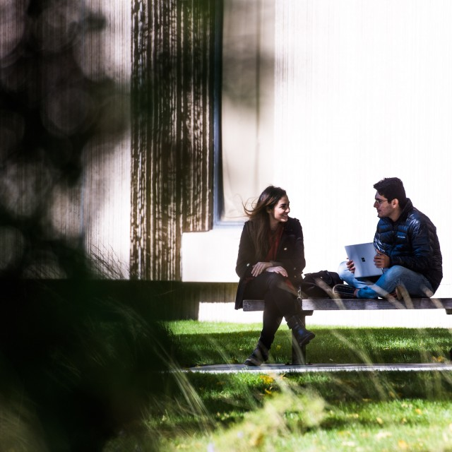 Two students wearing jackets sit on a bench outside talking on a sunny day.