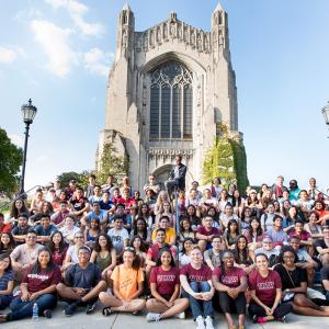 阳光明媚的一天,一大群学生在一座石头教堂前的楼梯上摆姿势合影.