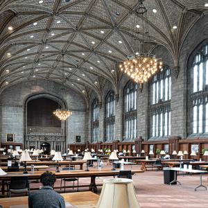 一个大的内部, 哥特式的房间有圆顶天花板和两个大吊灯显示, 学生们在有灯的桌子旁学习.