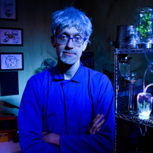 A man stands in a dark room lit with blue light with terrariums of plants on metal shelves in the background.