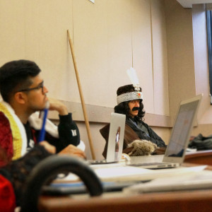 A student dressed as Vlad the Impaler with a feathered hat and a large mustache sits in a lecture hall among other students.