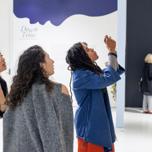 "A group of students look up at a painting in one of the Smart Museum's galleries. The wall behind them reads ""Down Time"" and has a blue graphic of a face in profile."