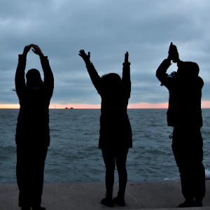 Silhouetted students stand on the shore of Lake Michigan doing yoga.