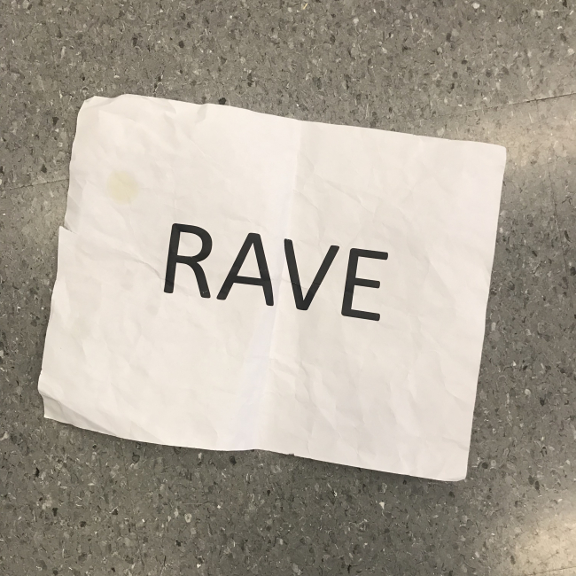 "The word ""RAVE"" is capitalized in black lettering on a wrinkled white piece of paper and placed against a speckled grey background."