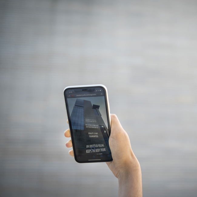 Hand holding a phone to a building with text on the phone