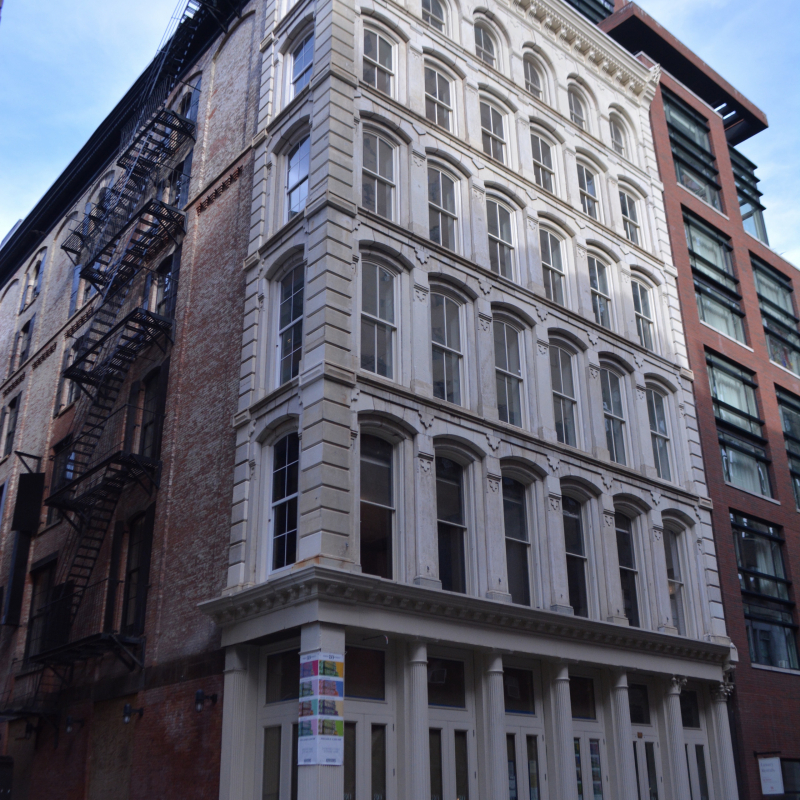 Artists Space at 11 Cortlandt Alley, New York [A six story building with a white facade is seen from the street in New York City.]
