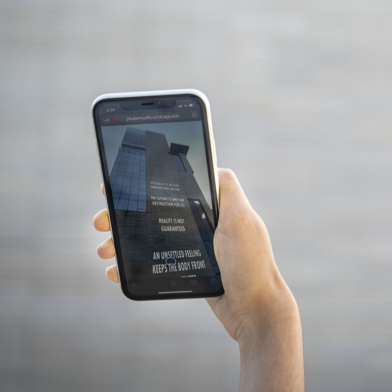 Hand holding a phone up to a building to see text on building