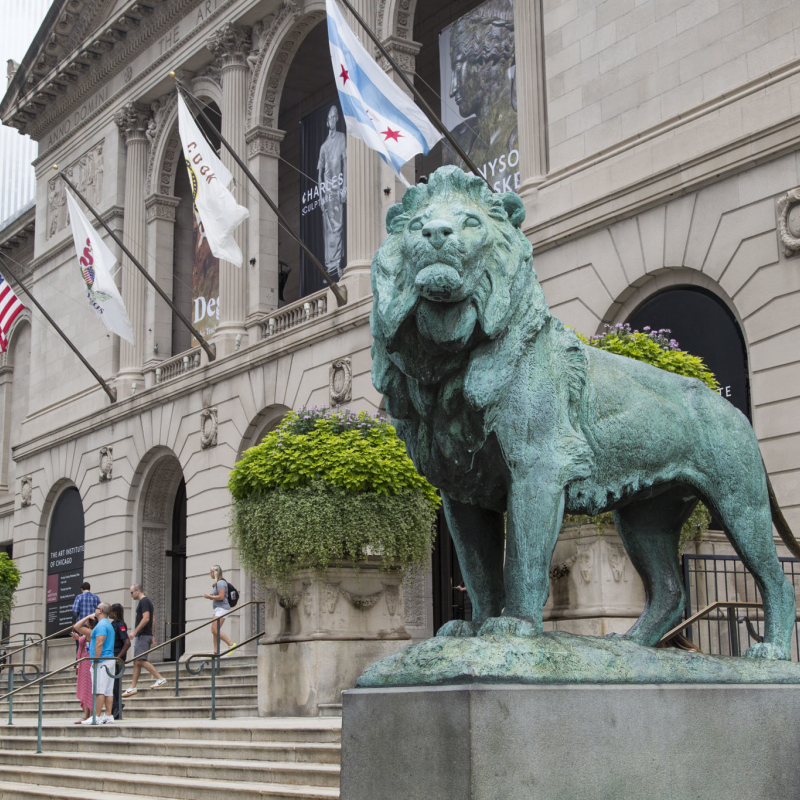 green lion statue in front of building