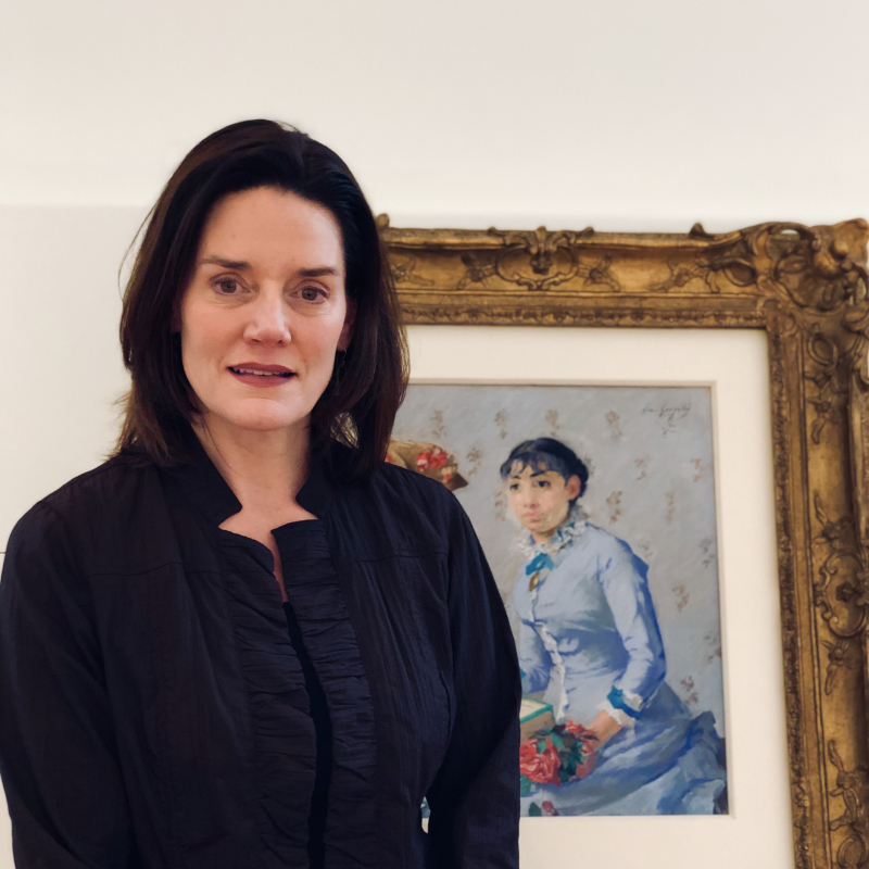Person wearing black in front of a painting