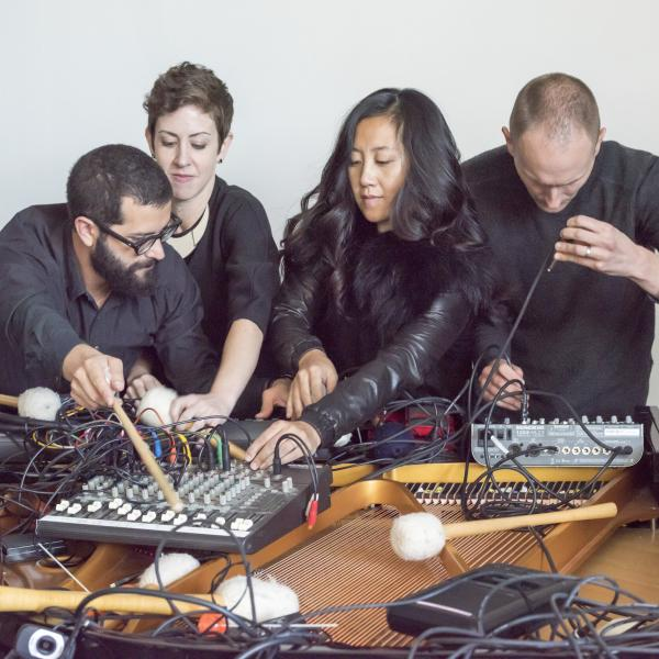 Yarn/Wire – Two men and two women lean over an open grand piano fighting over objects strewn across the stings, including electronics and percussion mallets