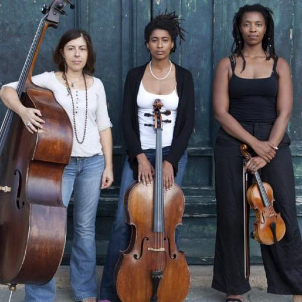 HEAR in NOW trio standing in front of a teal wall with bass, cello, and violin