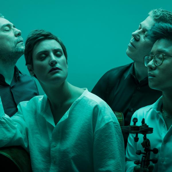 Members of string quartet Quatuor Diotima posing in blue-green light