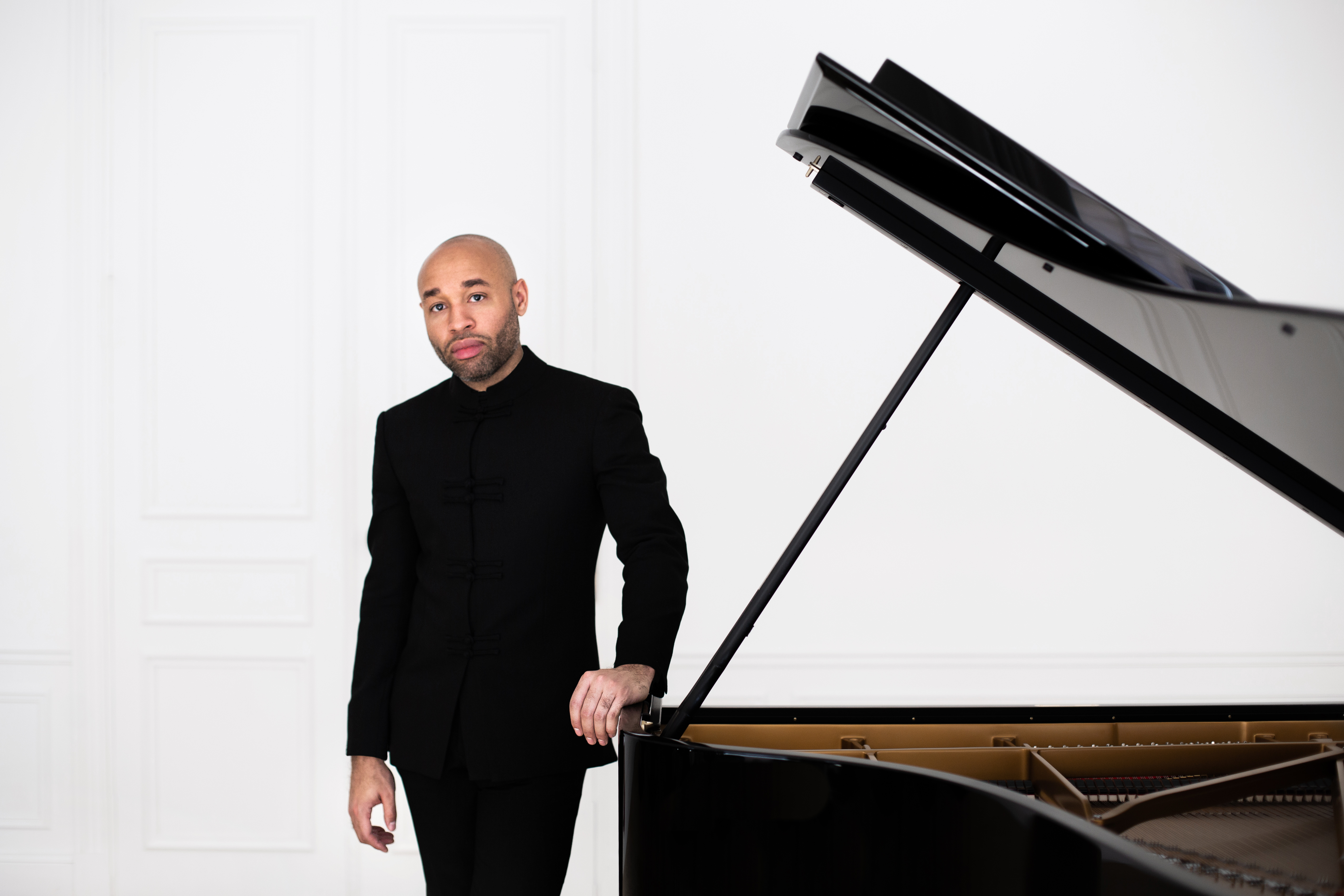 Aaron Diehl wears an all black suit standing next to a black steinway with open lid