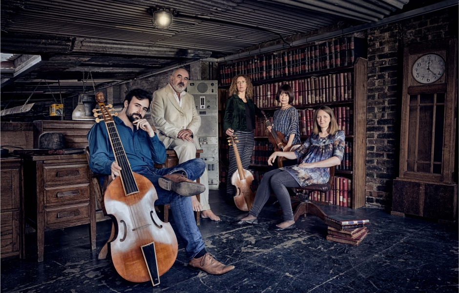 The members of Fretwork sit in a wood paneled library with instruments