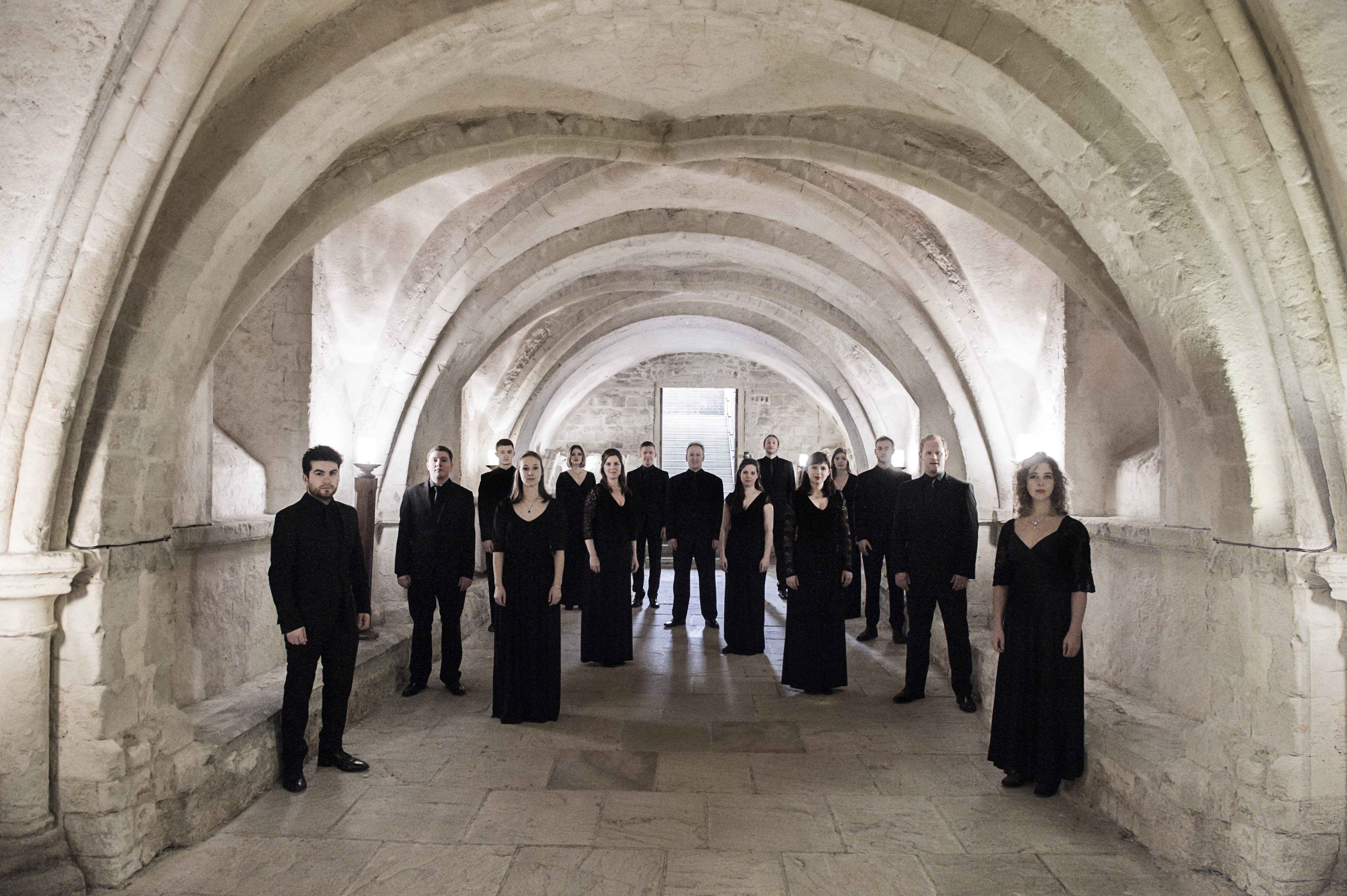 The members of the choir Tenebrae wearing black stand in a brightly lit stone vaulted hallway