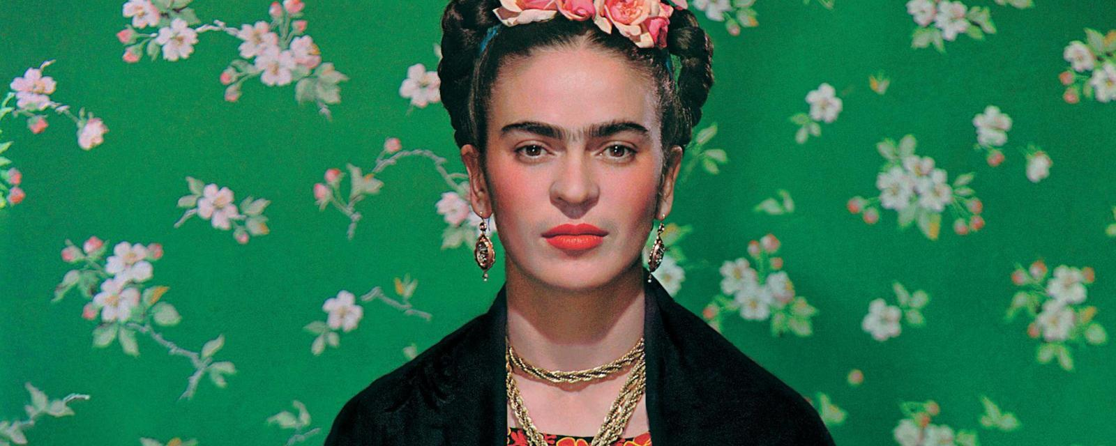 Artist Frida Kahlo seen in front of green wallpaper with floral print