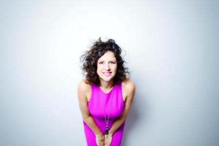 Anat Cohen wearing a bright pink dress and leaning toward the camera