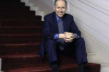 Michael Boriskin sitting on steps with a maroon rug