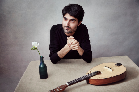 Alon Sariel sits at a table with a single flower in a black vase and a lute