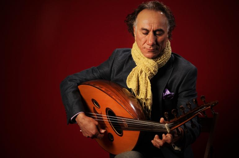 Rahim AlHaj playing oud, wearing a yellow scarf in front of a red background