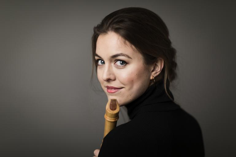 Tabea Debus looking over her shoulder and holding a recorder