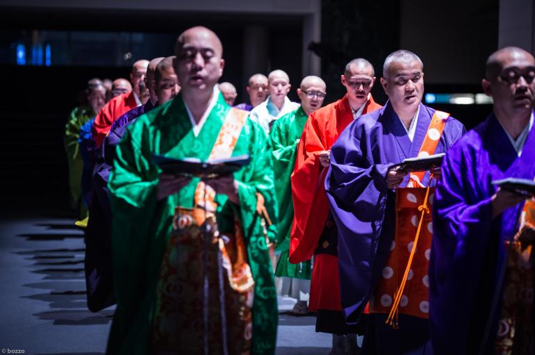 Shomyo no Kai –a group of men wearing brightly colored silk robes and standing in two lines chant while holding open books