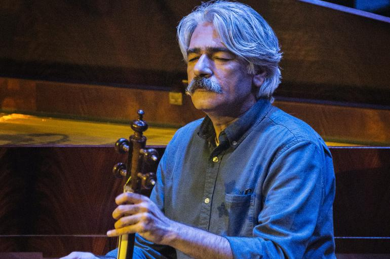 Kayhan Kalhor playing kamancheh onstage in blue light with eyes closed