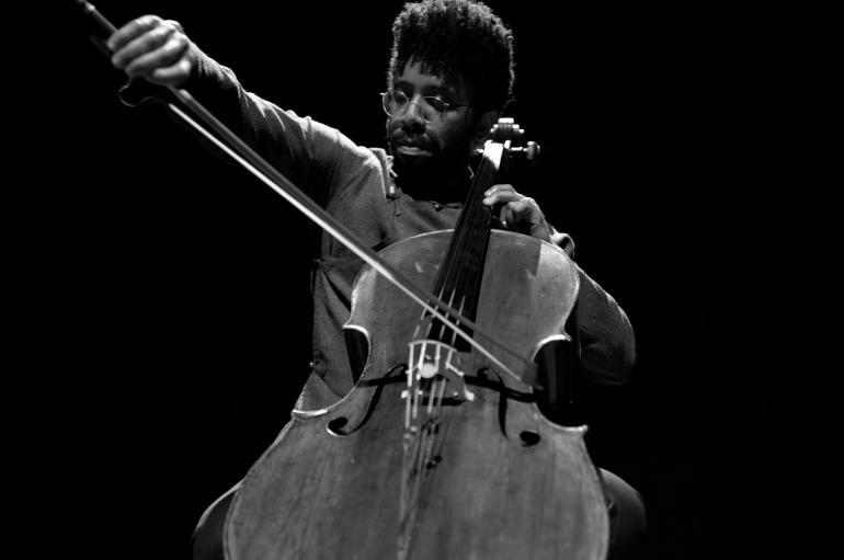 Low-angle black and white photo of Seth Parker Woods and cello mid-performance