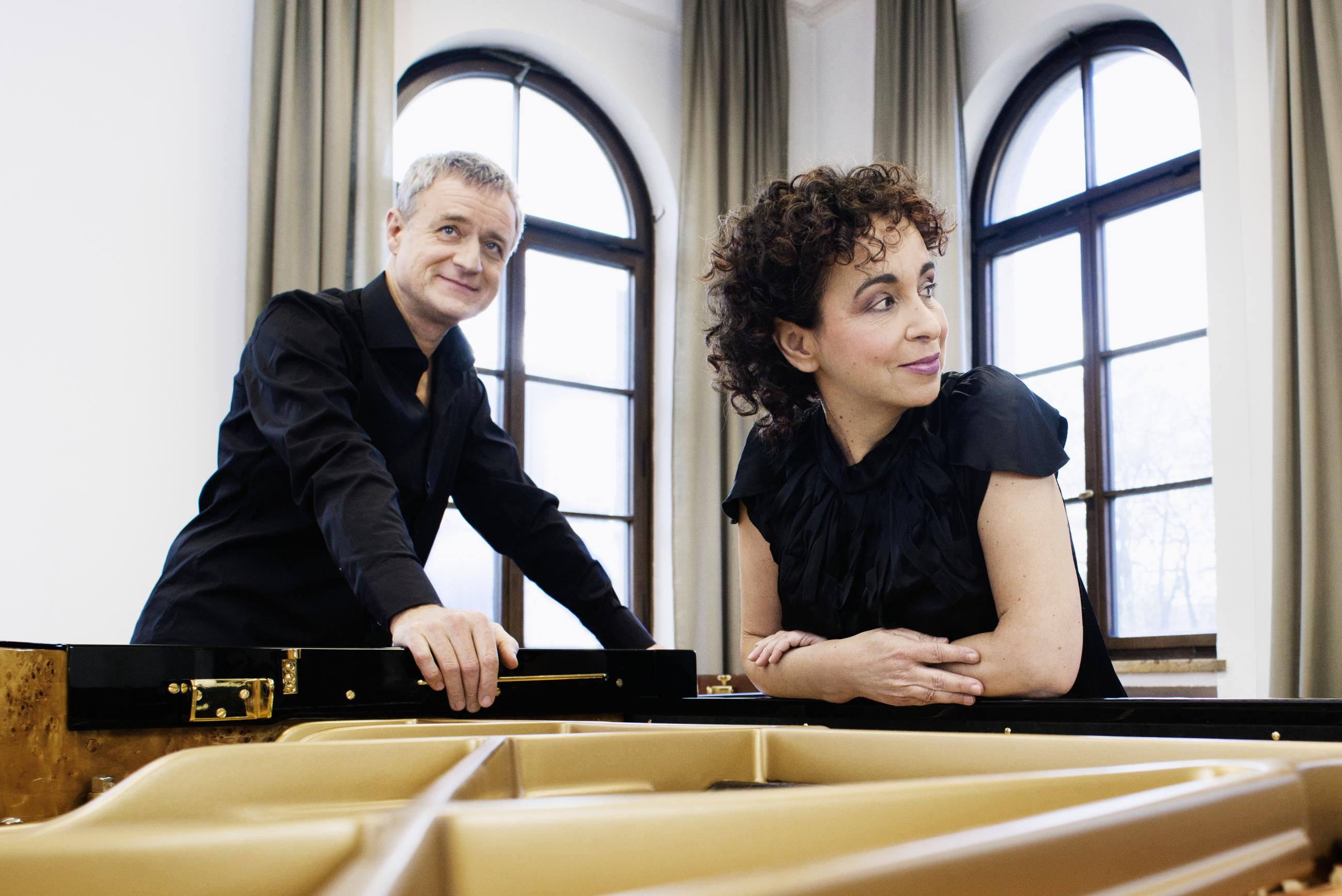 Duo Tal and Groethuysen leaning over an open grand piano