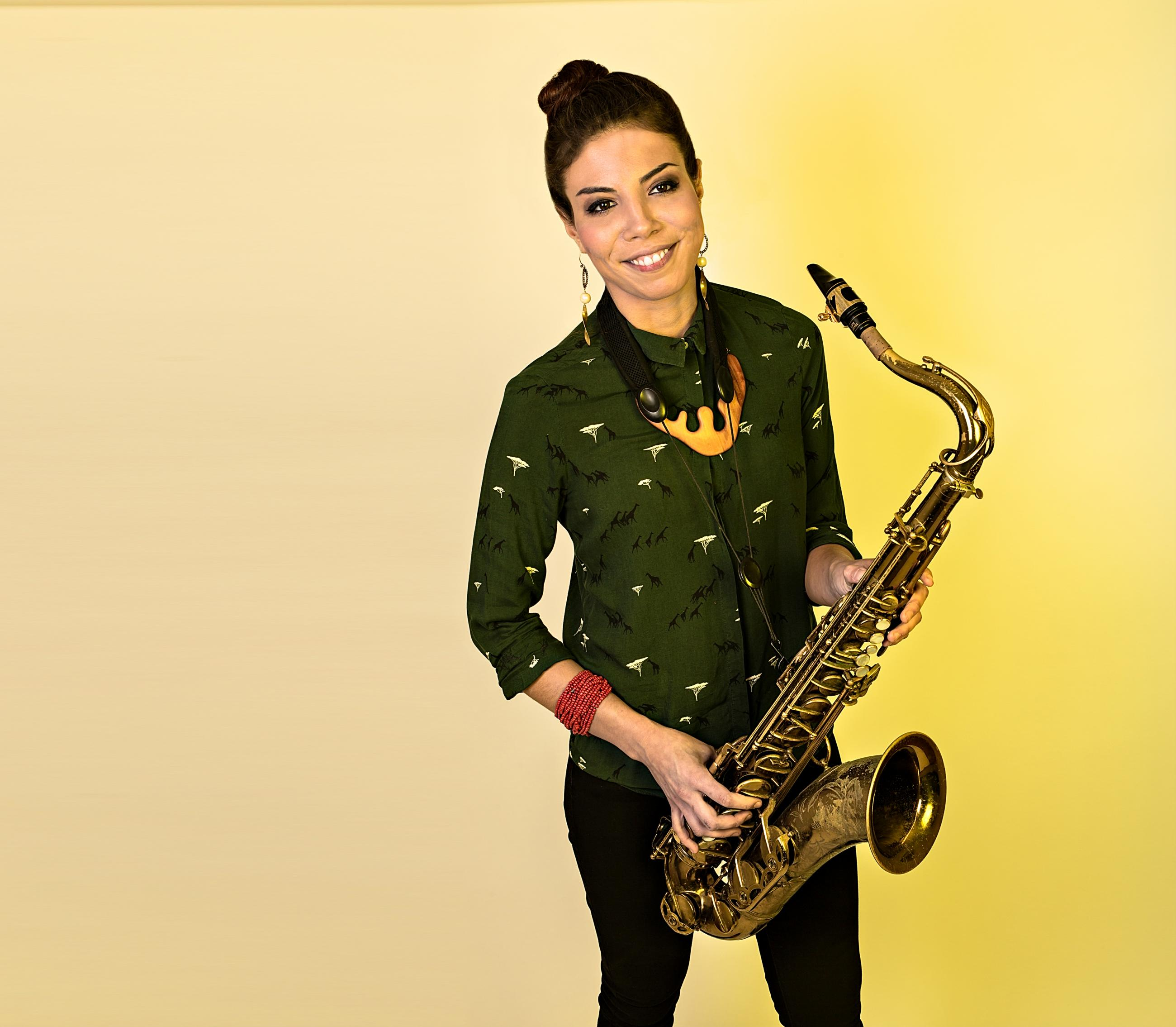 Melissa Aldana standing in front of yellow wall holding tenor saxophone
