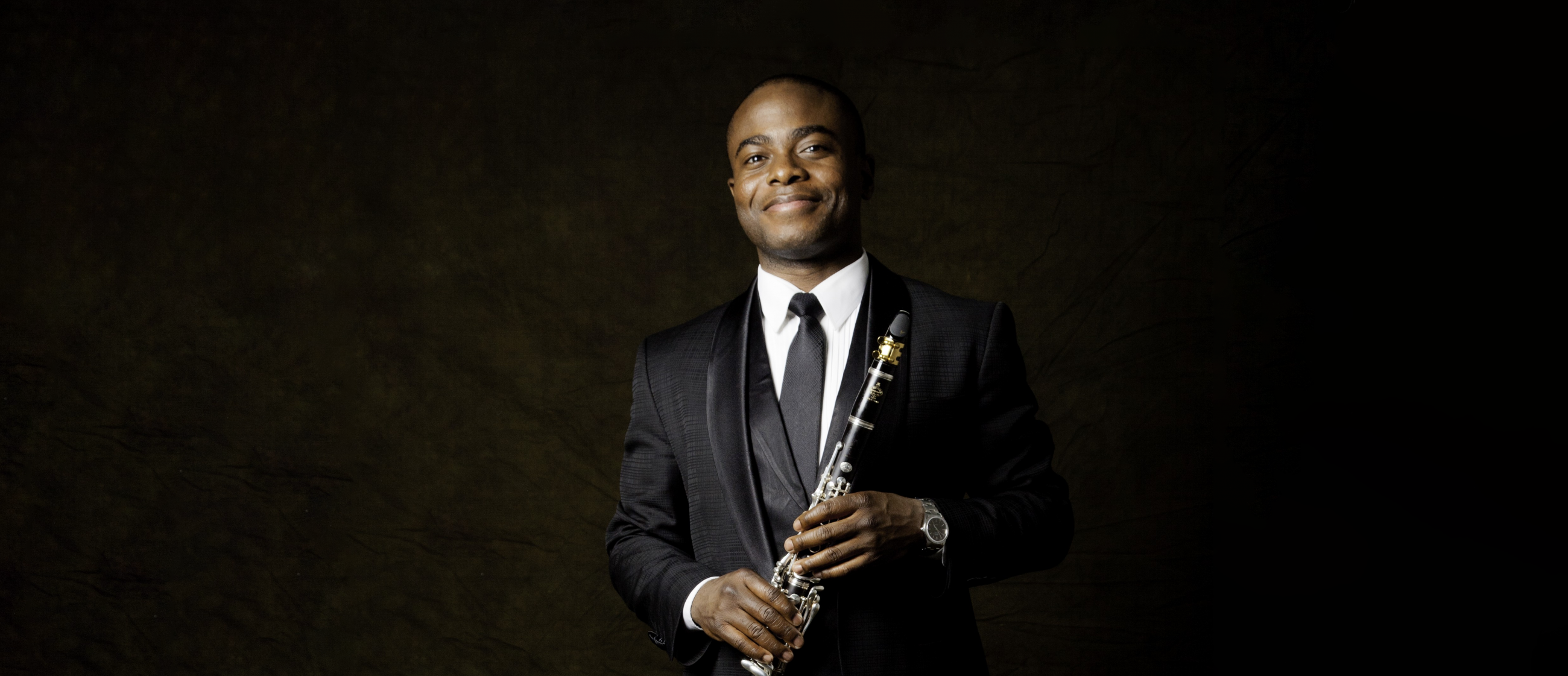 Anthony McGill wears a black suit with white shirt and black tie holding his clarinet