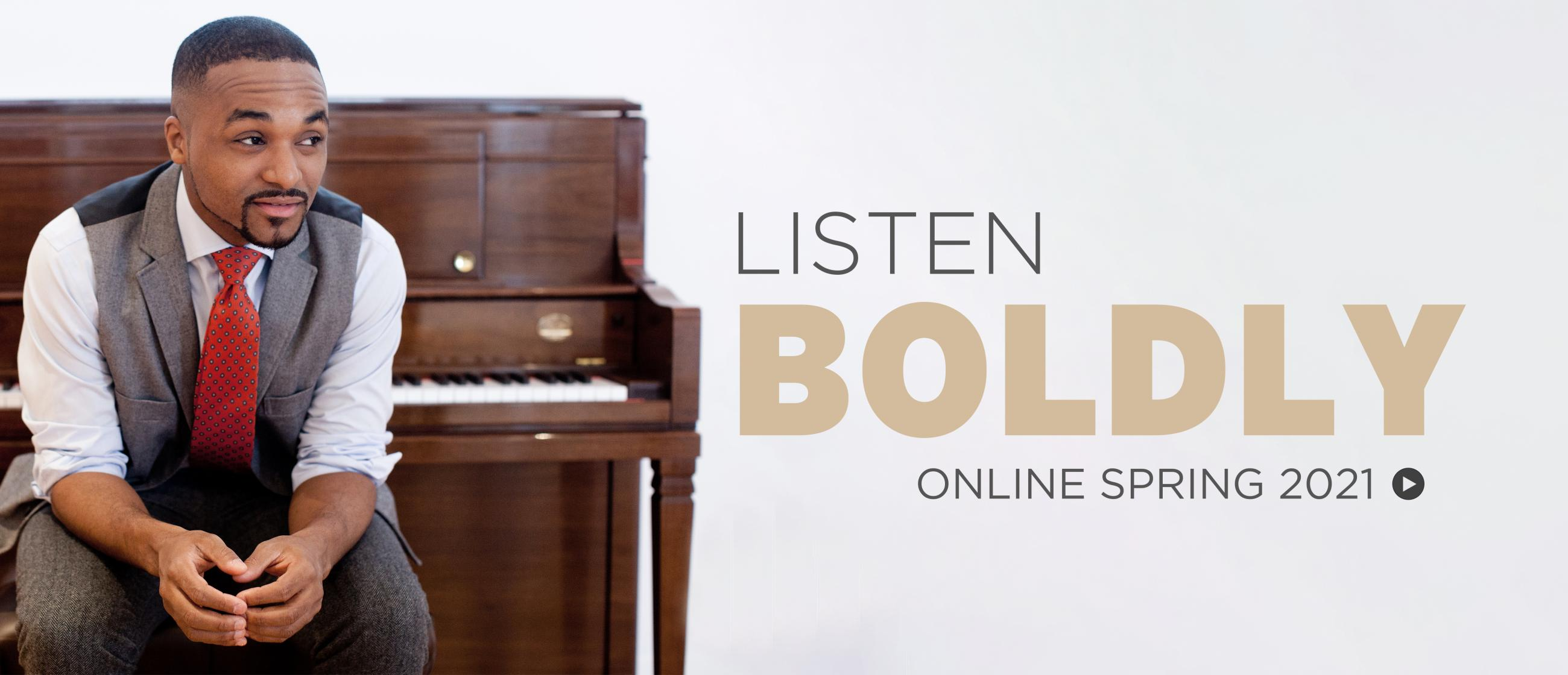 Photo of Sullivan Fortner, a black man wearing grey trousers and a grey waistcoat with a red tie, sitting on a piano bench in front of a brown upright piano. Text reads Listen Boldly, Online Spring 2021.