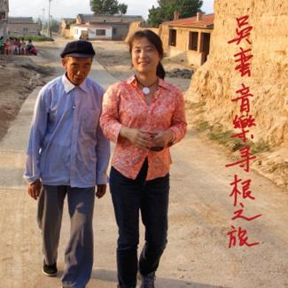 Wu Man walks with an elderly Chinese man down a dirt road